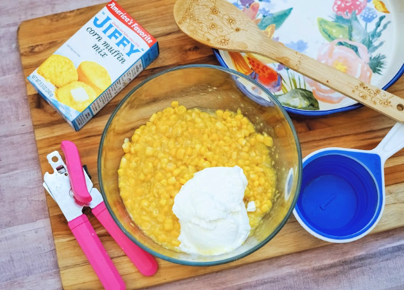 mixing bowl with two kinds of corn and sour cream add to be mixed together for corn casserole