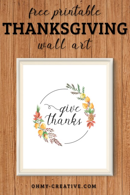 "A framed ""Give Thanks"" printable decoration for Thanksgiving. Displayed on a woodbackground"