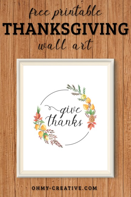 """A framed """"Give Thanks"""" printable decoration for Thanksgiving. Displayed on a woodbackground"""