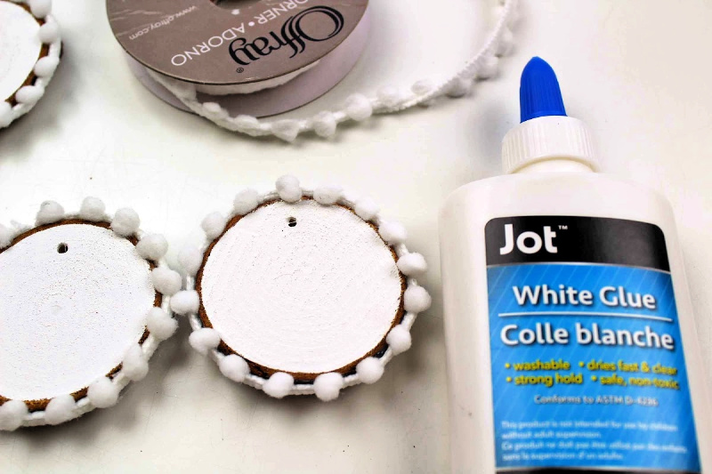 Wood Slices painted white with white pom pom trim glued around wood slice for showman ornament craft