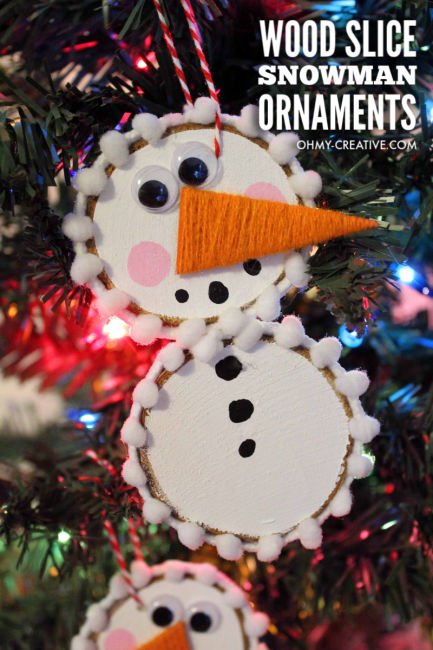finished wood slice snowman ornament on a Christmas tree with colored lights