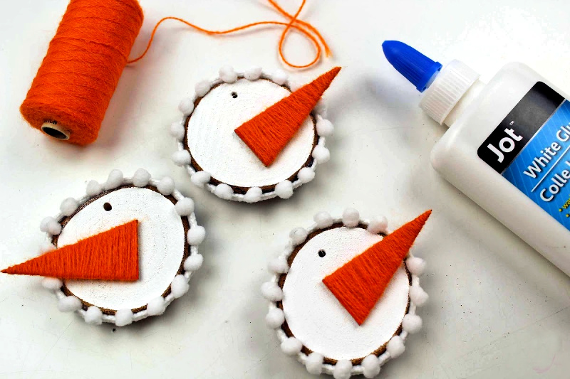 Wood Slices painted white with orange carrot nose, holes with for string to complete showman ornament