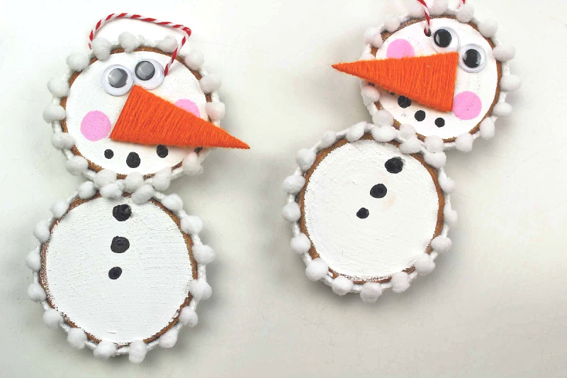 finished wood slice snowman ornament on a white background