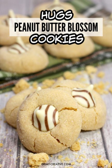 Peanut butter blossom cookies made with Hershey Hugs Kisses on a wood plank background. A try of cookies is seen in the background.