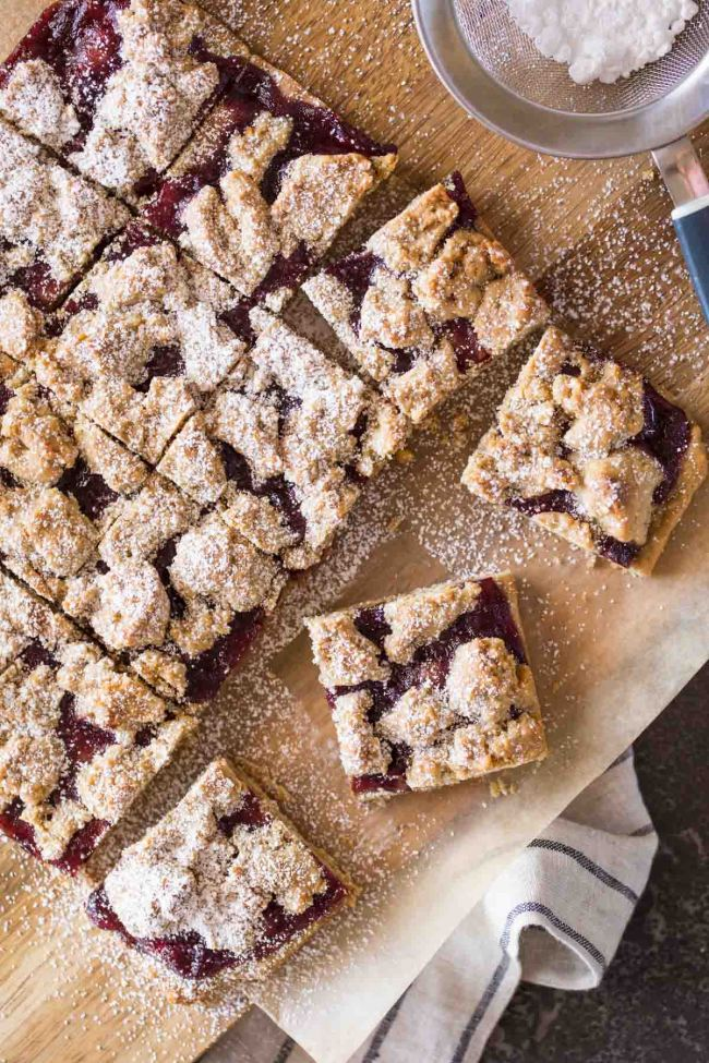 Square Oat bars made with a purple or red jelly and peanut butter inside.