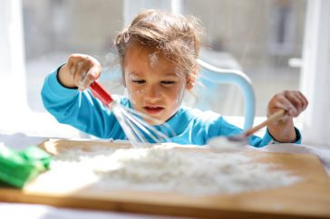 little girl with a whisk and flour with a wood cutting board