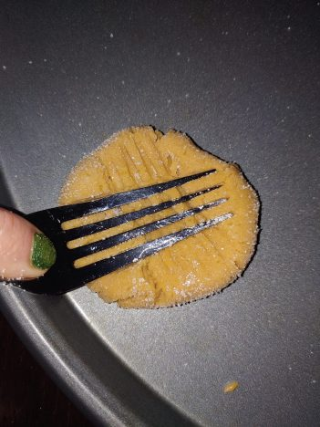 metal fork pressing into a peanut butter cookie