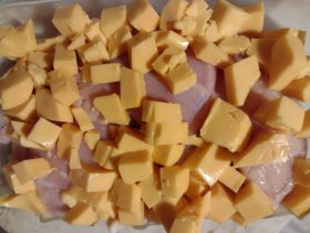 cubed cheese layered over raw chicken breasts