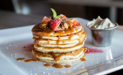 pancakes topped with strawberries and syrup on a white platter
