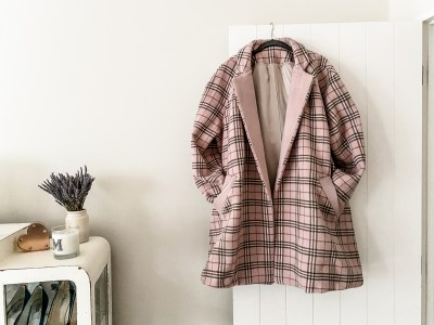 image of new deer and doe opium coat hanging on a door. Made by oh sew fearless using a blush check wool, lined with a matching silk