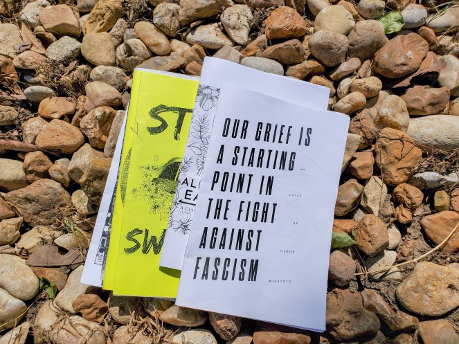 Photo: A collection of zines from the Virtual Gonzo Zine Library sitting on a bed of gravel.