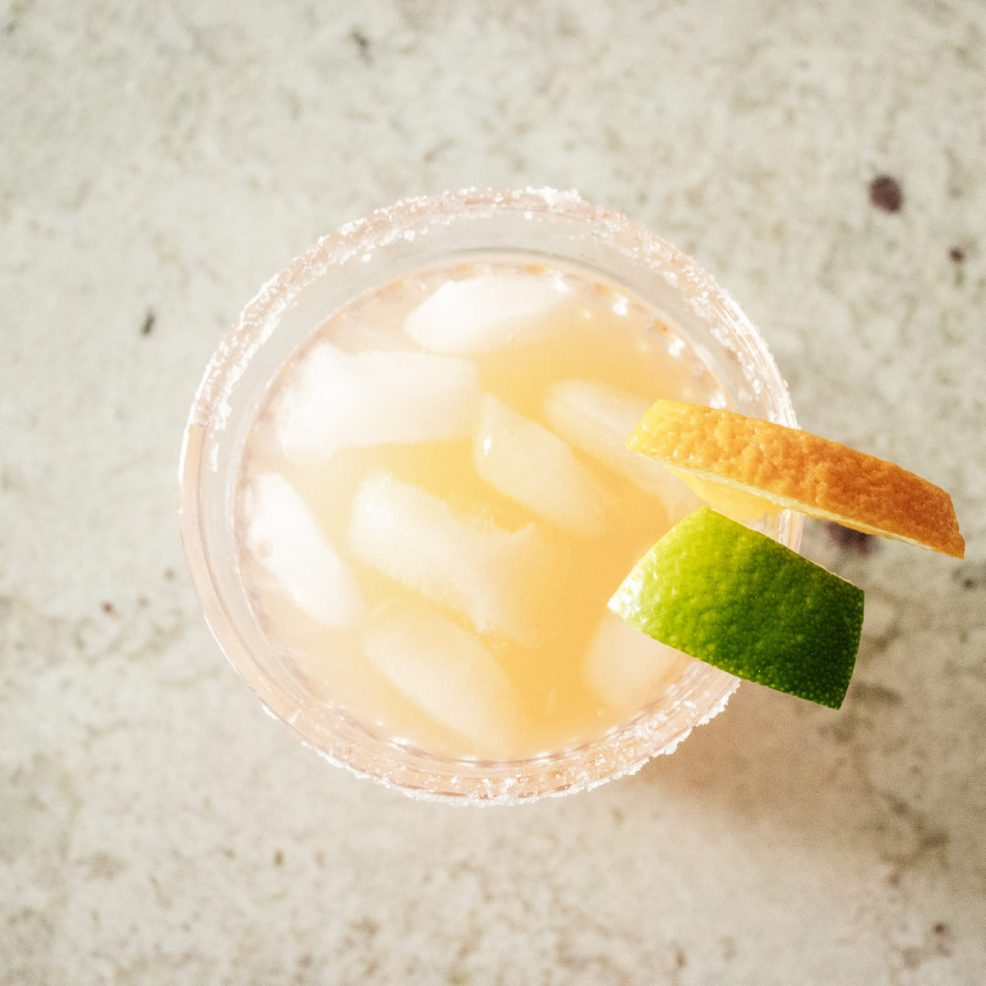 overhead view of a paloma in a glass, garnished with a lime and an orange.