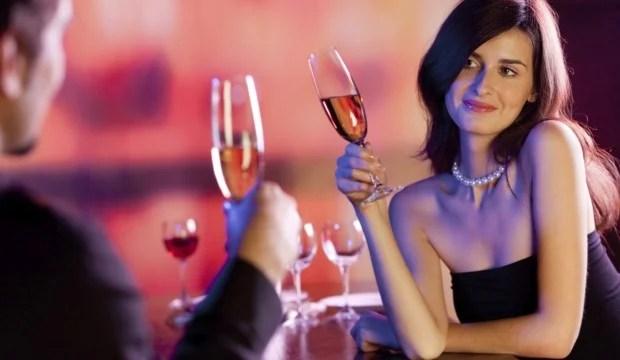 dos personas sosteniendo una copa mientras tienen una platica
