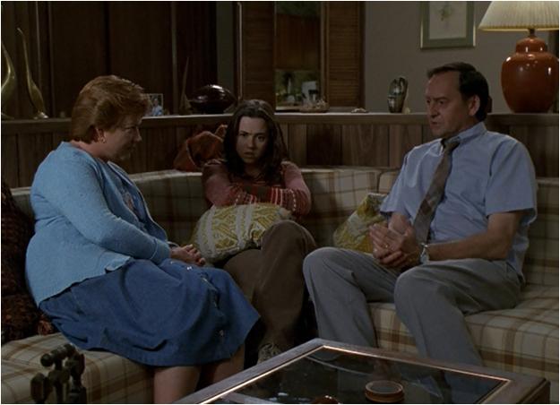 padres sentados hablando con su hija en la sala