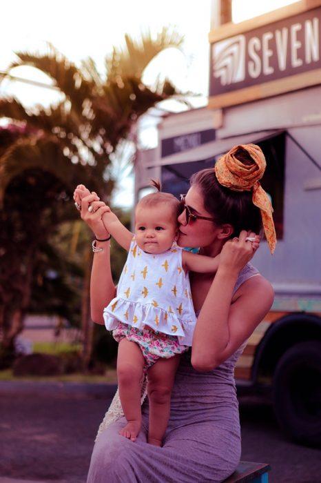 Mujer sosteniendo a una bebé entre sus brazos mientras le besa la mejilla