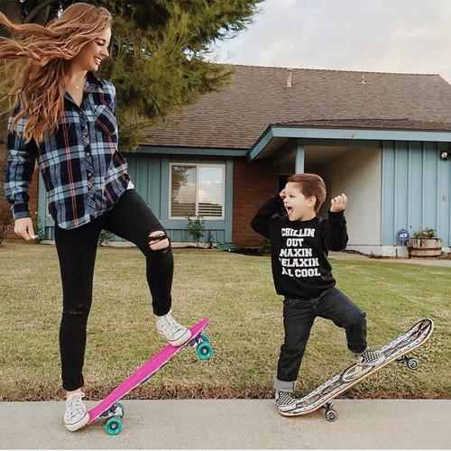 chica y niño sobre una patineta jugando en la calle