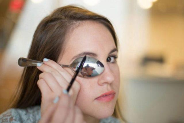 Chica delineando sus cejas con la ayuda de una cuchara