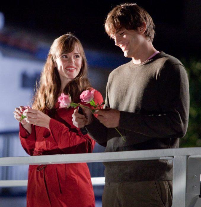 pareja en un muelle flores en la mano sonriendo