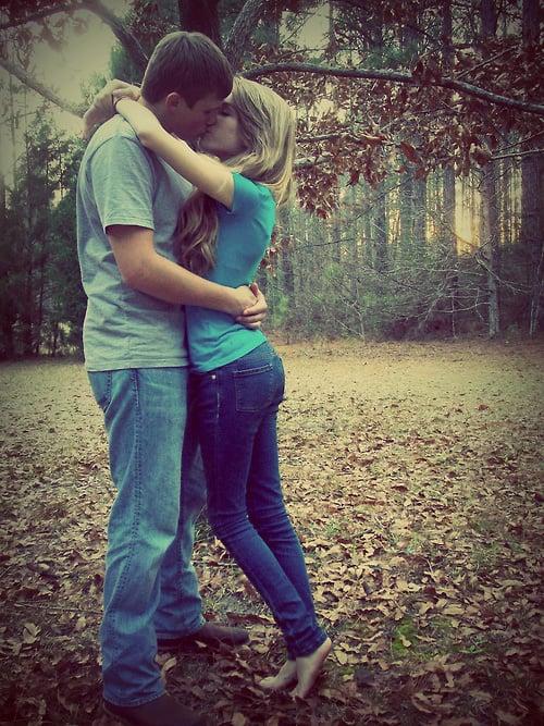 pareja besándose entre las hojas