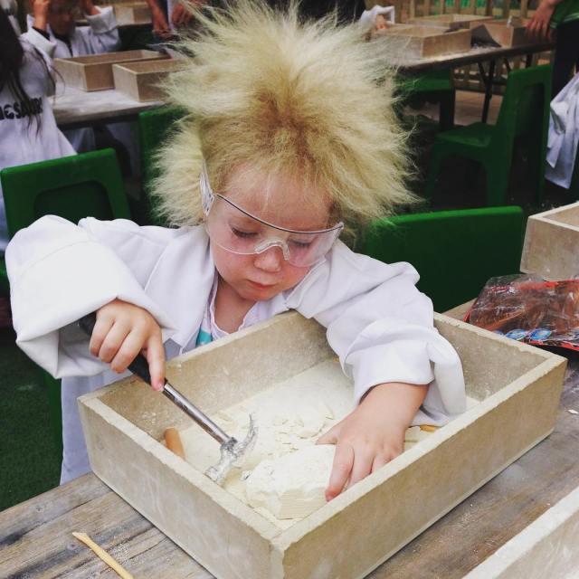 niña co bata de laboratorio martillando