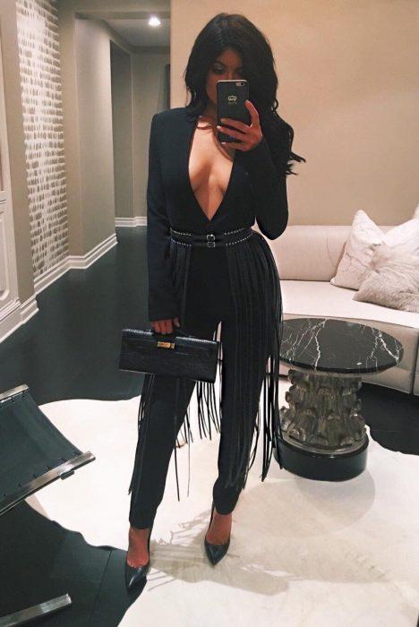 Chica usando un jumpsuit de color negro con un cinturón de correas