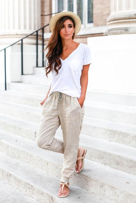 Looks de primavera; mujer de cabello castaño, ondulado y largo, con sombrero de mimbre, blusa blanca básica y pantalón beige holgado de lino delgado y sandalias de piso