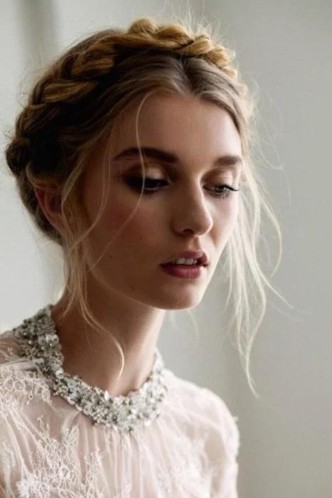 Ideas de peinados para el calor; mujer rubia con peinado de corona despeinada de trenza y blusa de encaje blanco