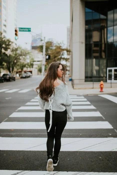 Chica caminando a punto de cruzar una avenida