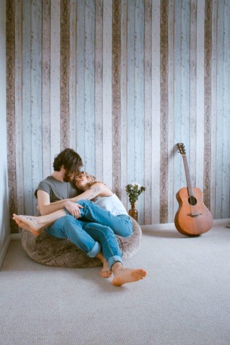 Pareja sentada en el suelo abrazándose y besándose