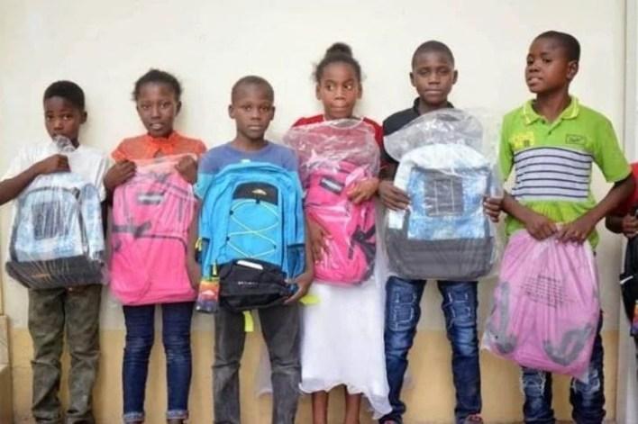 Chicos de haití sosteniendo varias mochilas en sus manos