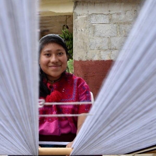 Mexican indigenous woman weaving on a cotton loom
