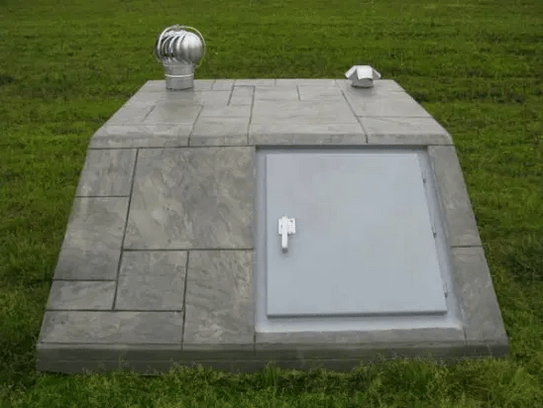 A concrete shelter installed in a backyard.