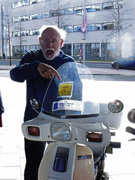 Mortified! One of the Wobblers points to the parking ticket on his Yamaha Town Mate.