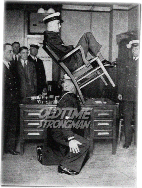 John Hajnos, The Navy Hercules, balances a fellow officer in a chair clenched between his teeth