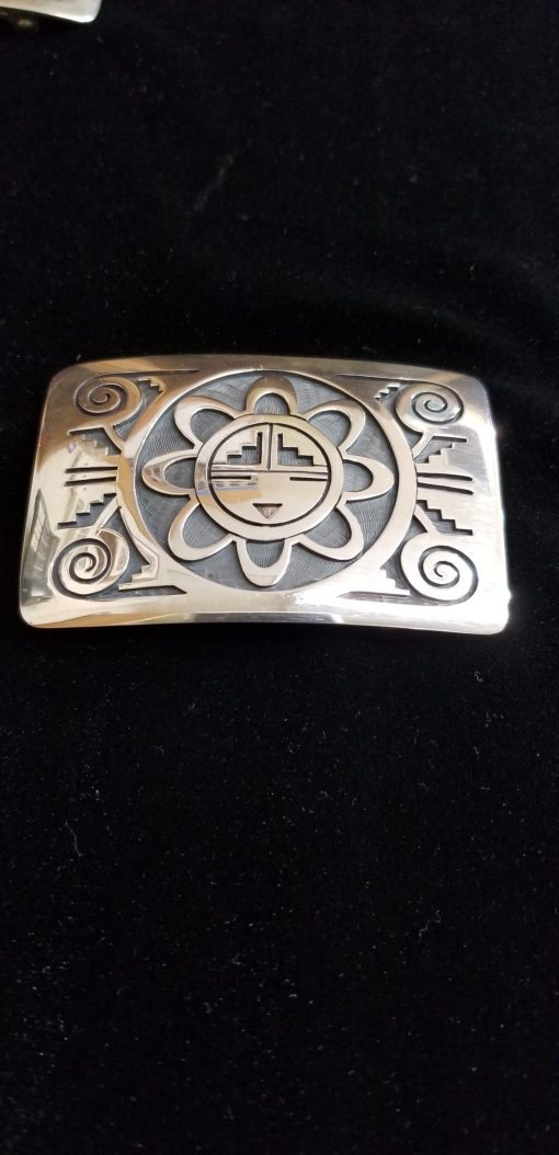 Hopi buckle with Sun Face by Augustine Moya also represents the water & warrior marks with thunder clouds around the sun's rays.