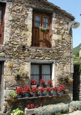 Altes Haus mit Blumen vor den Fenstern in Beget
