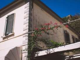 Rote Blüten ranken am toskanischen Haus