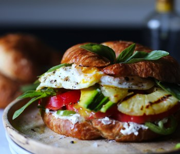 Croissant and fried egg sandwich with avocado and grilled pineapple