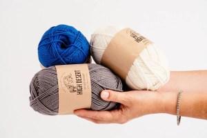 hands holding three balls of yarn
