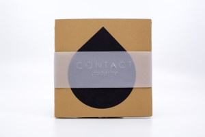 "Image description: A small, square book cover with a black teardrop shape in the centre, and a thin translucent slip with ""CONTACT"" in English text and Braille embossed on the front."