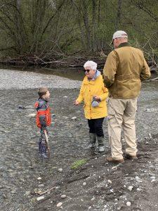 Grandma and Grandpa outside near the stream with grandson
