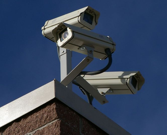 Surveillance cameras on the corner of a building.