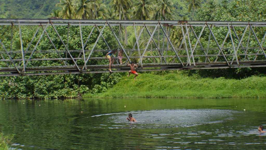 Children jumping off Teahupoo beach on a Tahiti road trip