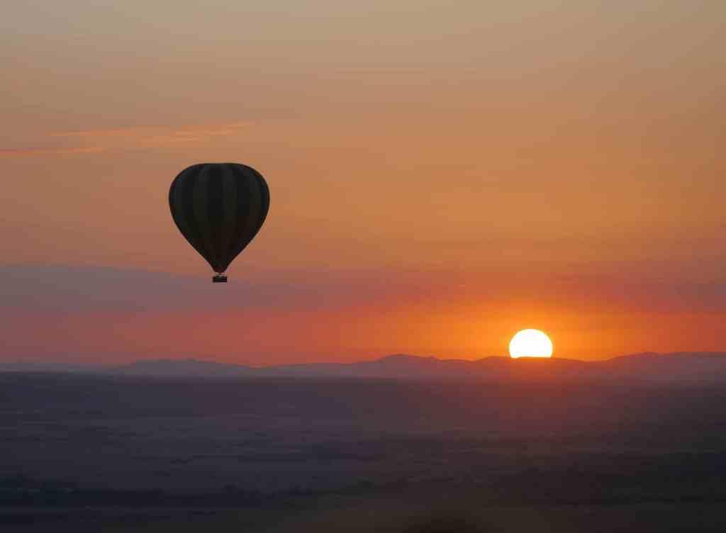 Sunrise behind a hot air balloon over the Maasai Mara