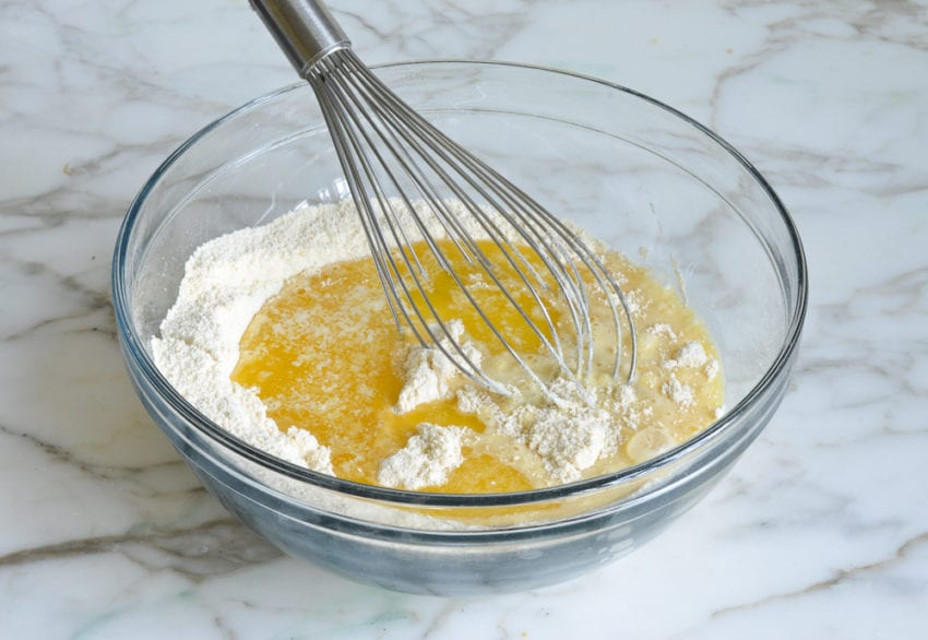 adding liquid ingredients and melted butter to dry ingredients