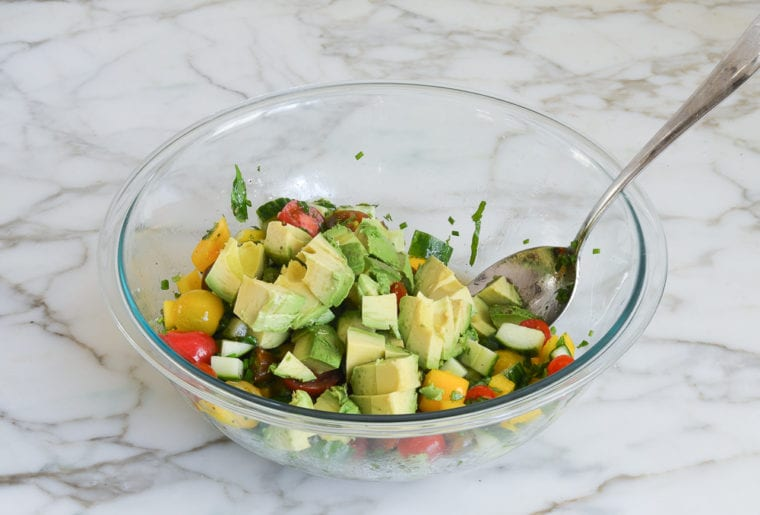 adding the avocados to the salad