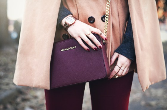 Brown cape burgundy jeans shoulder bag boots and furry hat michael kors
