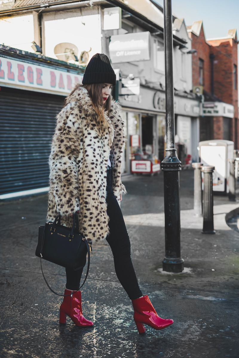 Stivaletti rossi in vinile e una pelliccia leopardata | Red vinyl ankle boots and animalier faux fur