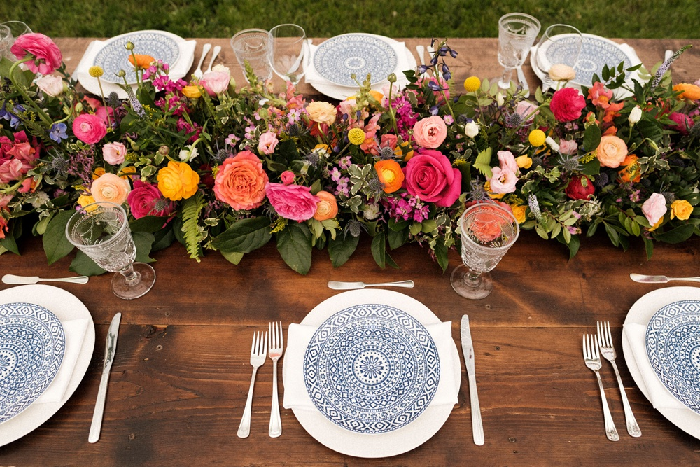 Table settings, decor and vibrant flowers by Lumme Creations at a wedding in Boulder.