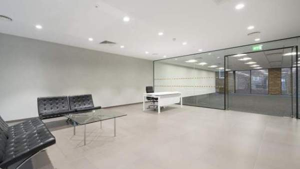 stylish pinned leather sofa chairs in a waiting area with glass coffee table and glass wall entrance to the office space